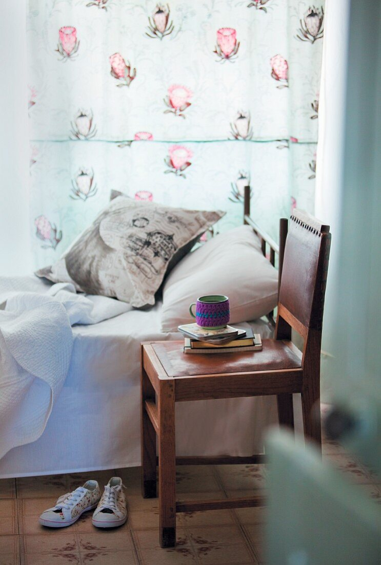 Bedroom with single bed, floral curtain, scatter cushion and leather chair as bedside table