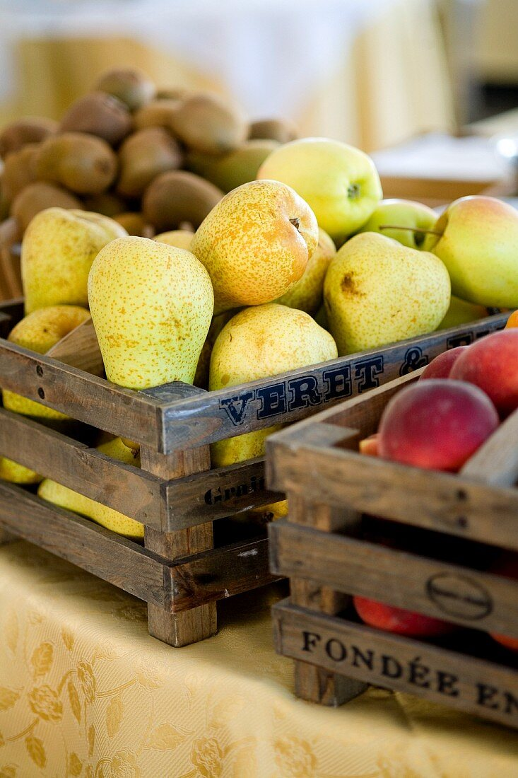 A wooden box of pears, between a box of nectarines and one of kiwis