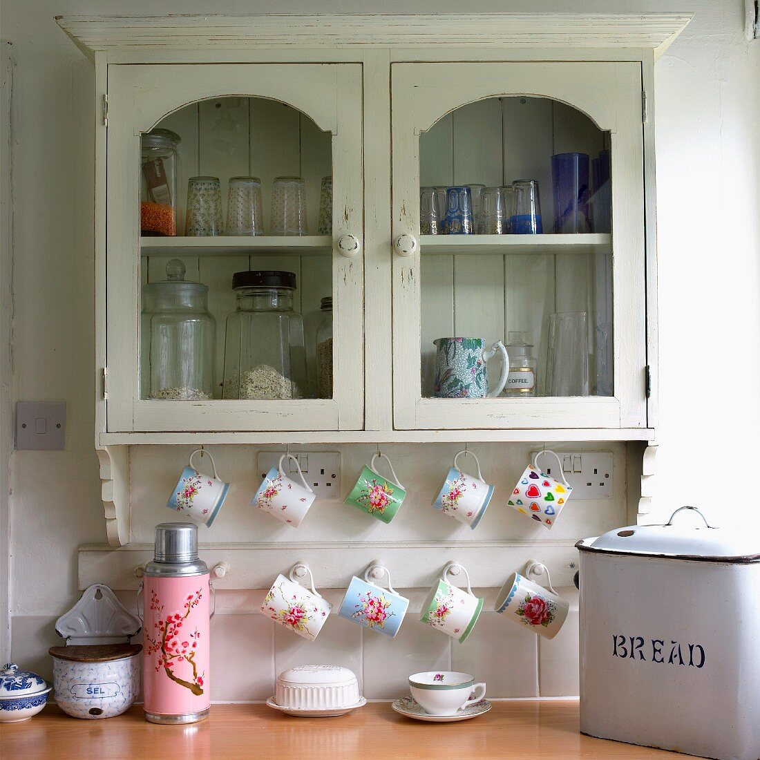 Floral patterns on thermos and cups hanging from rack below old, wall-mounted cabinet in vintage kitchen