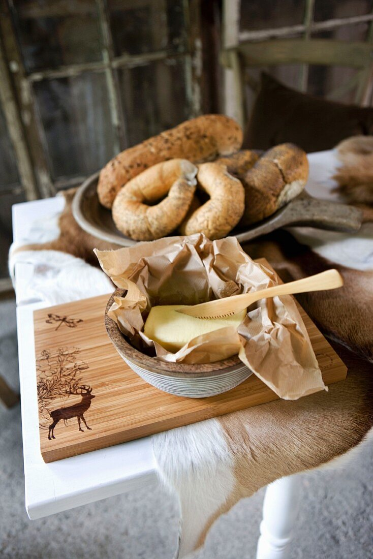 Wooden knife in butter dish on wooden chopping board in front of bread rolls in ceramic dish on table covered with animal skin
