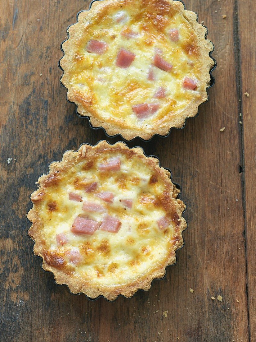 Two Quiche Lorraine on a Wooden Table