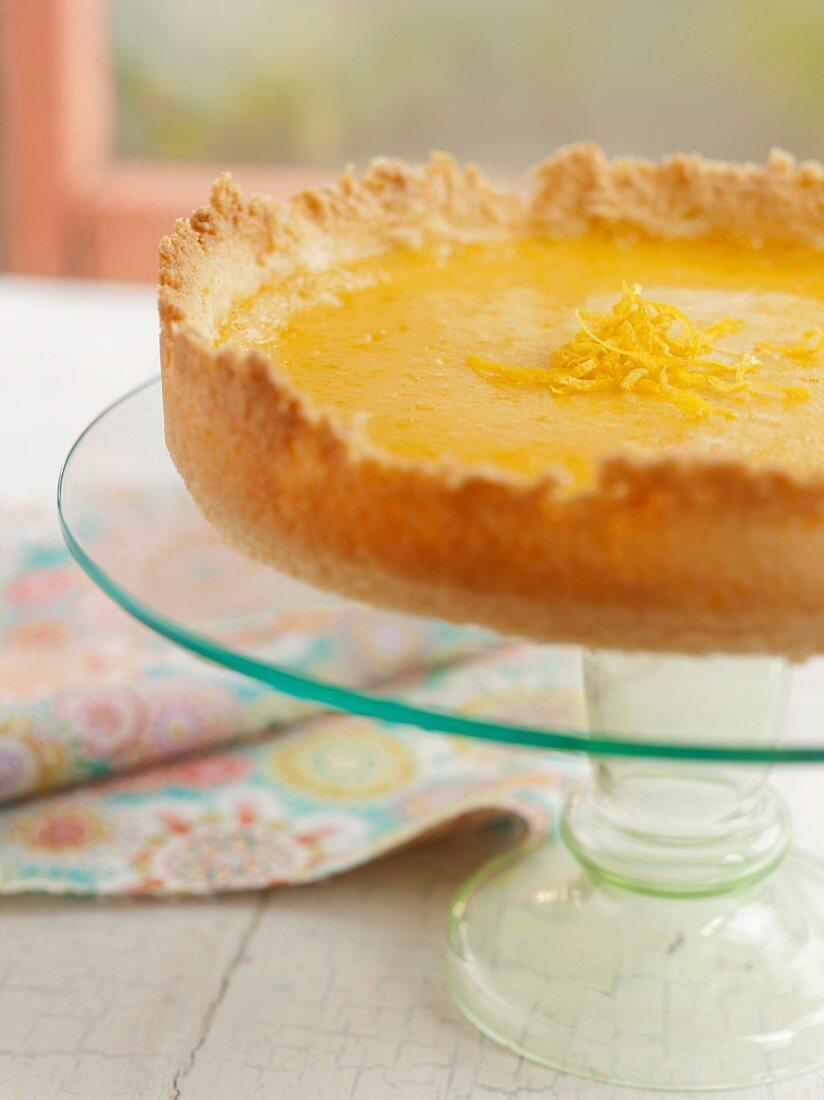 A Whole Lemon Tart on a Glass Pedestal Dish; Window in Background