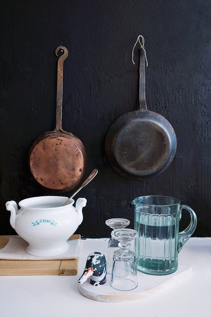 Jug of water, glasses and soup tureen in front of vintage pans hanging on black wall