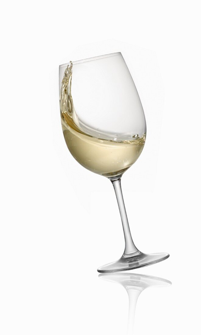 A tilting glass of white wine