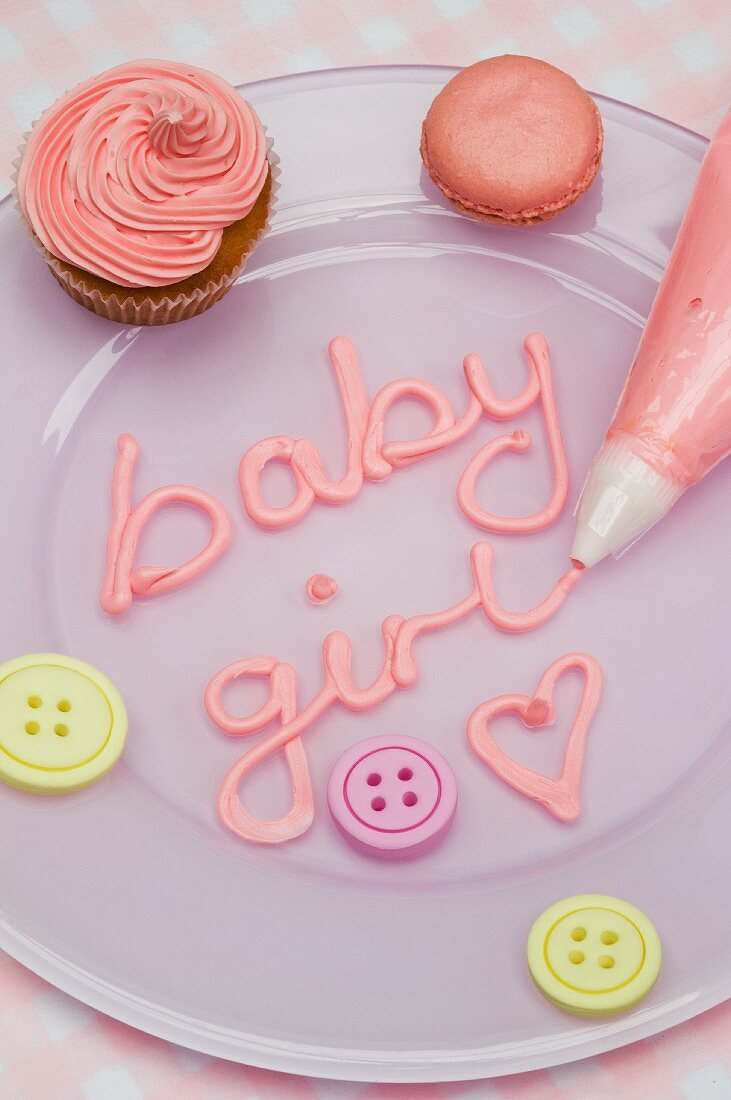 A pink cupcake, macaroons and letters iced with a piping bag for a baby shower