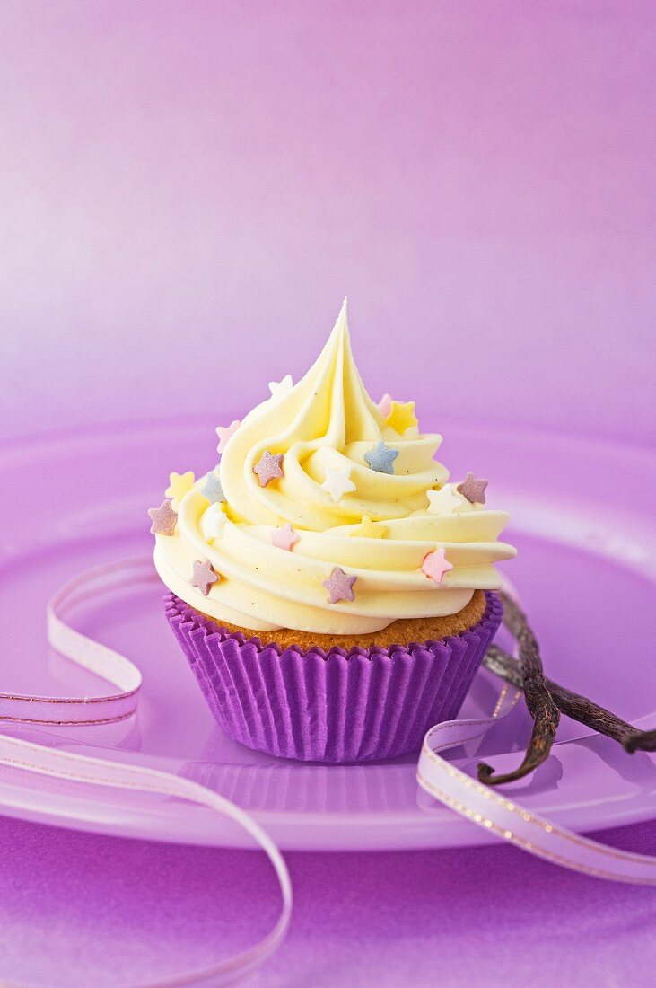 A vanilla cupcake with colourful sugar stars on a purple plate with a ribbon