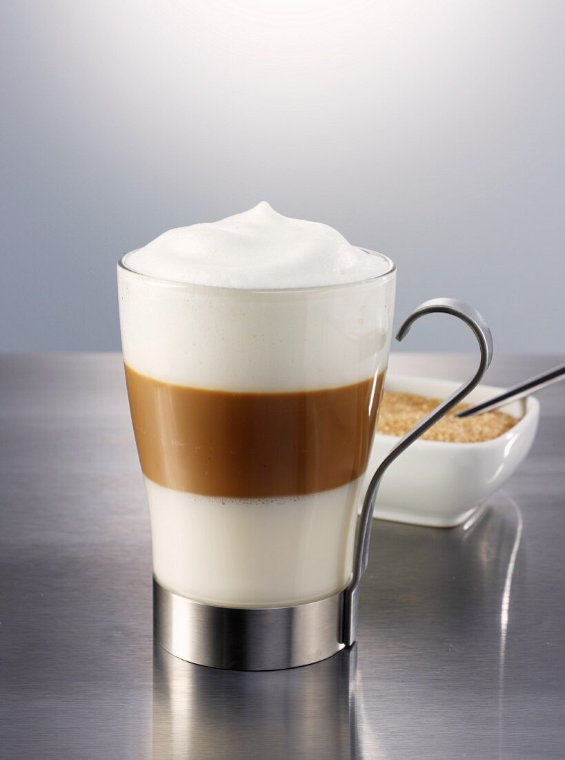 A latte macchiato with a bowl of sugar