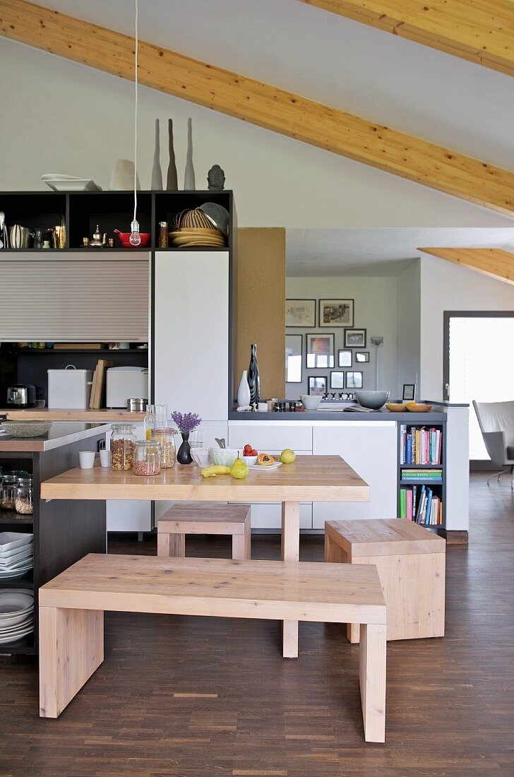 Pale wooden bench and stools at dining table in open-plan, modern kitchen with wood-beamed ceiling