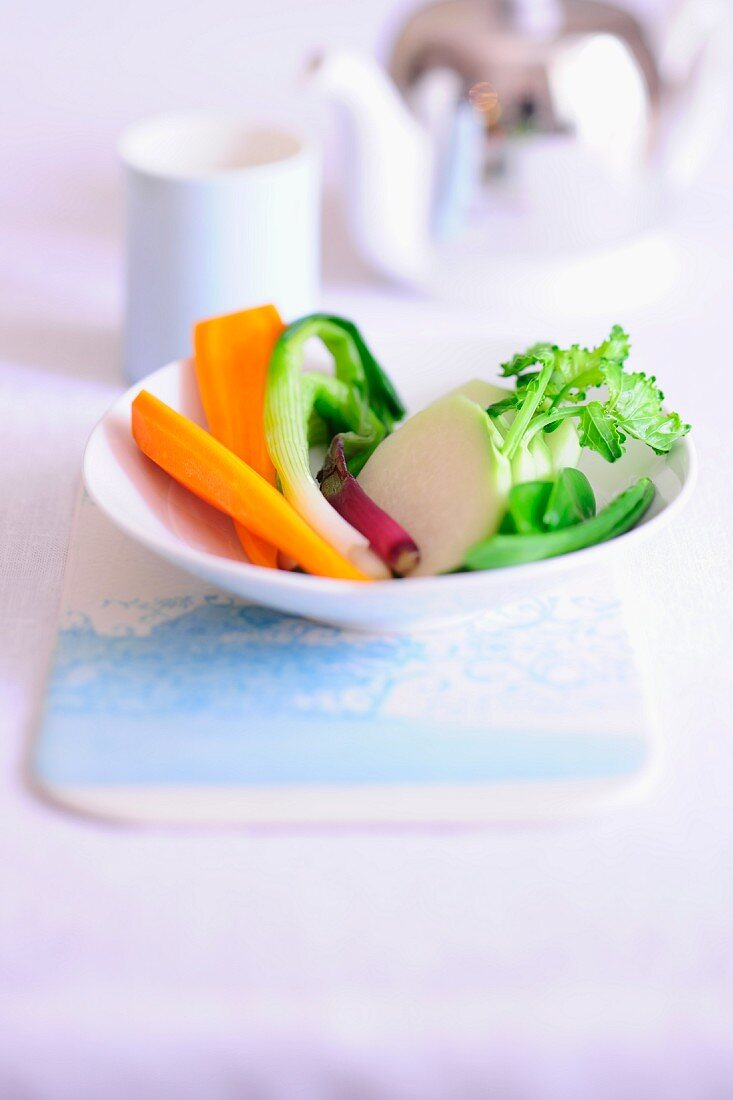 A plate of crudités including carrots, spring onion, kohlrabi and sugar snap peas
