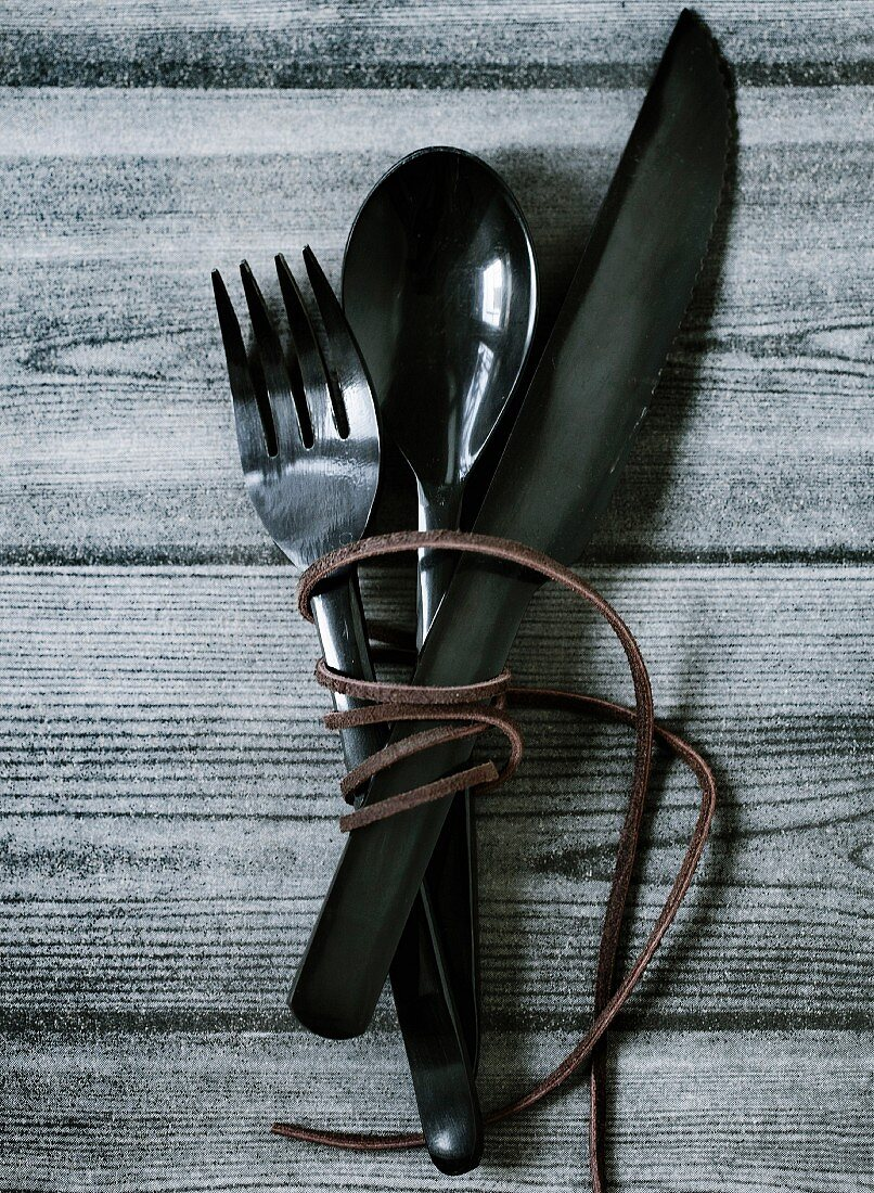 A leather thong wound around a set of cutlery, on a wooden table