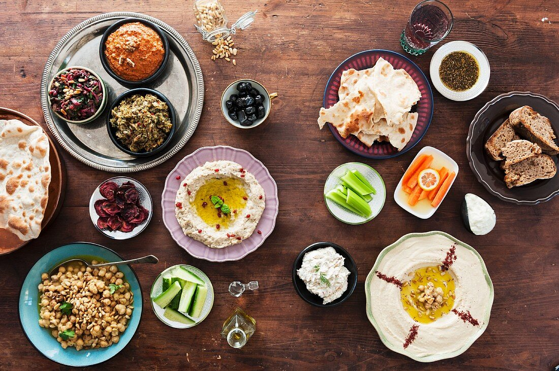 An assortment of Middle Eastern dips with bread, olives and vegetables