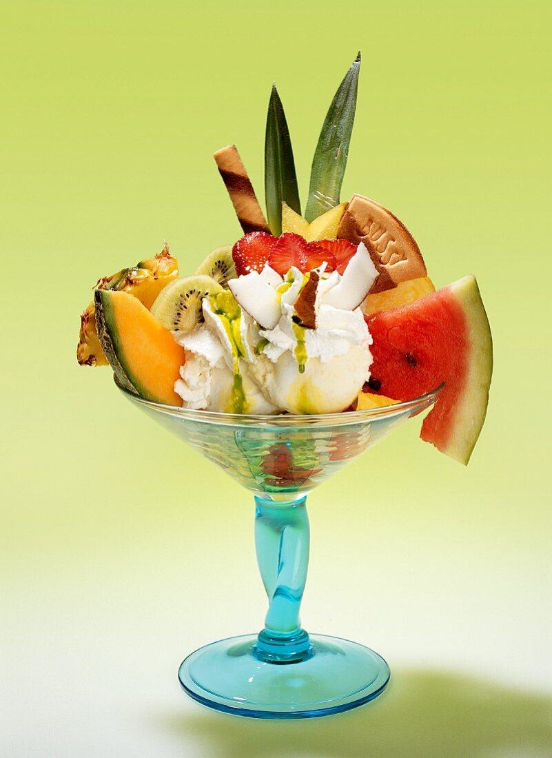 A fruit sundae with lemon ice cream, fresh fruits, cream and wafers