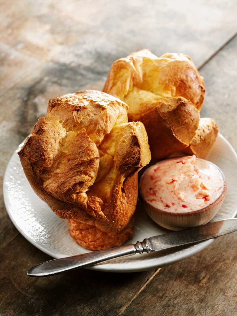 Two Popovers with Strawberry Butter and an Antique Knife on a White Plate
