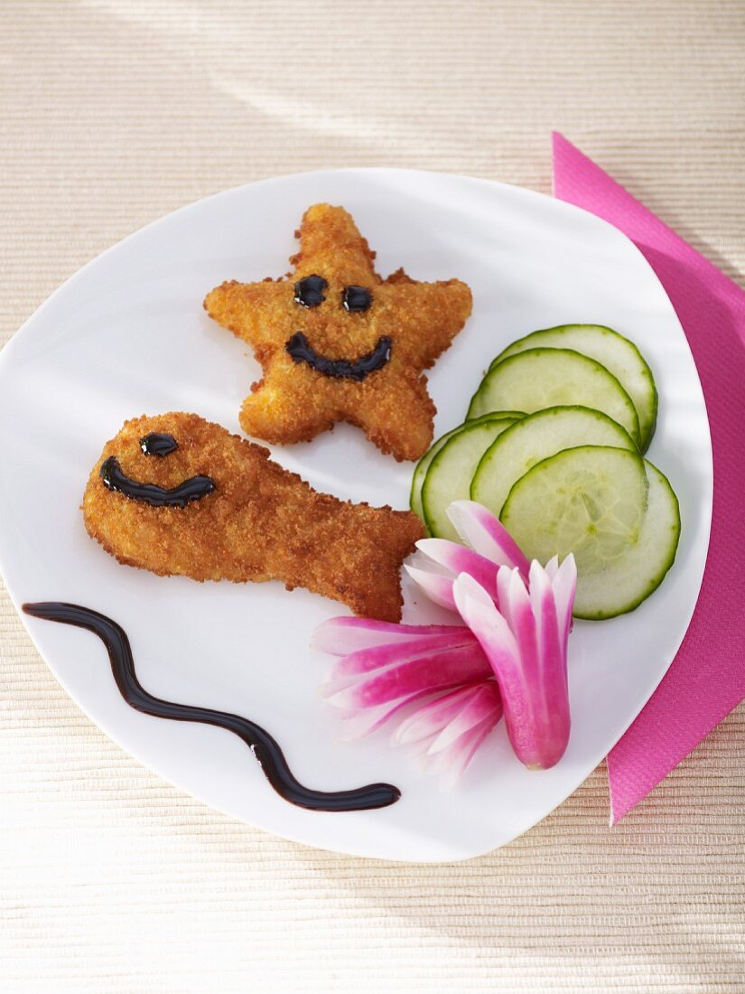 Breaded fish with smiley faces, radish flowers and balsamic reduction
