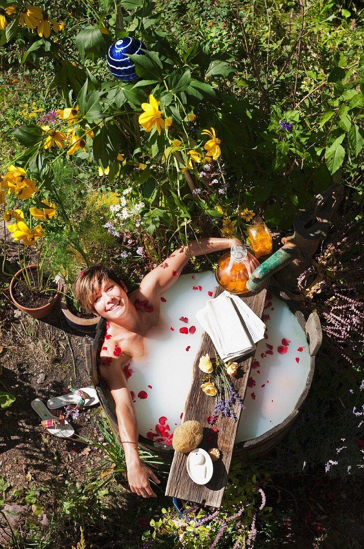 A woman having a milk bath in a wooden tub in the garden