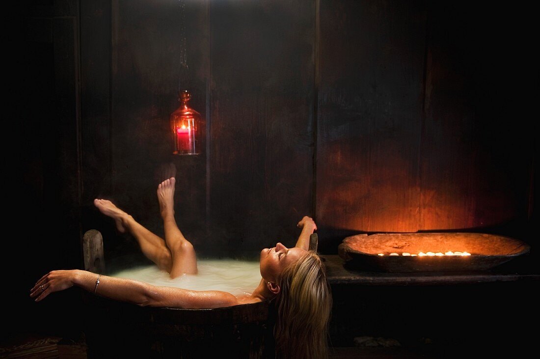 Woman bathing in wooden bathtub in candlelight