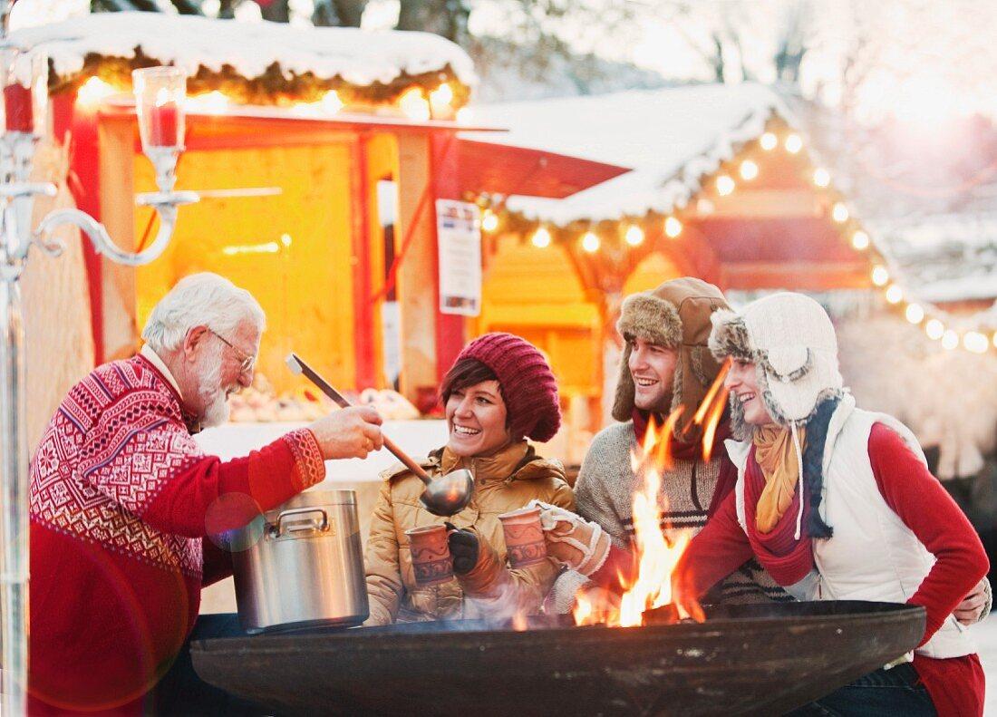 Älterer Mann serviert Punsch bei einem Weihnachtsmarkt