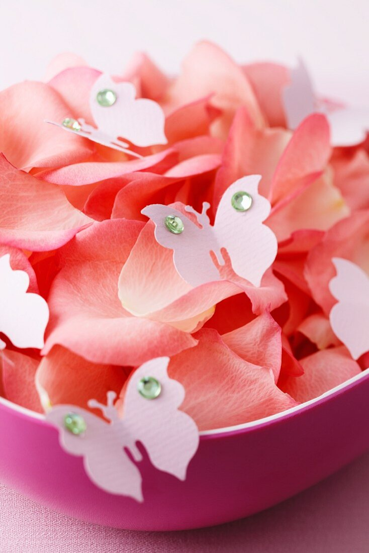 Flower petals and decorative butterflies in a bowl