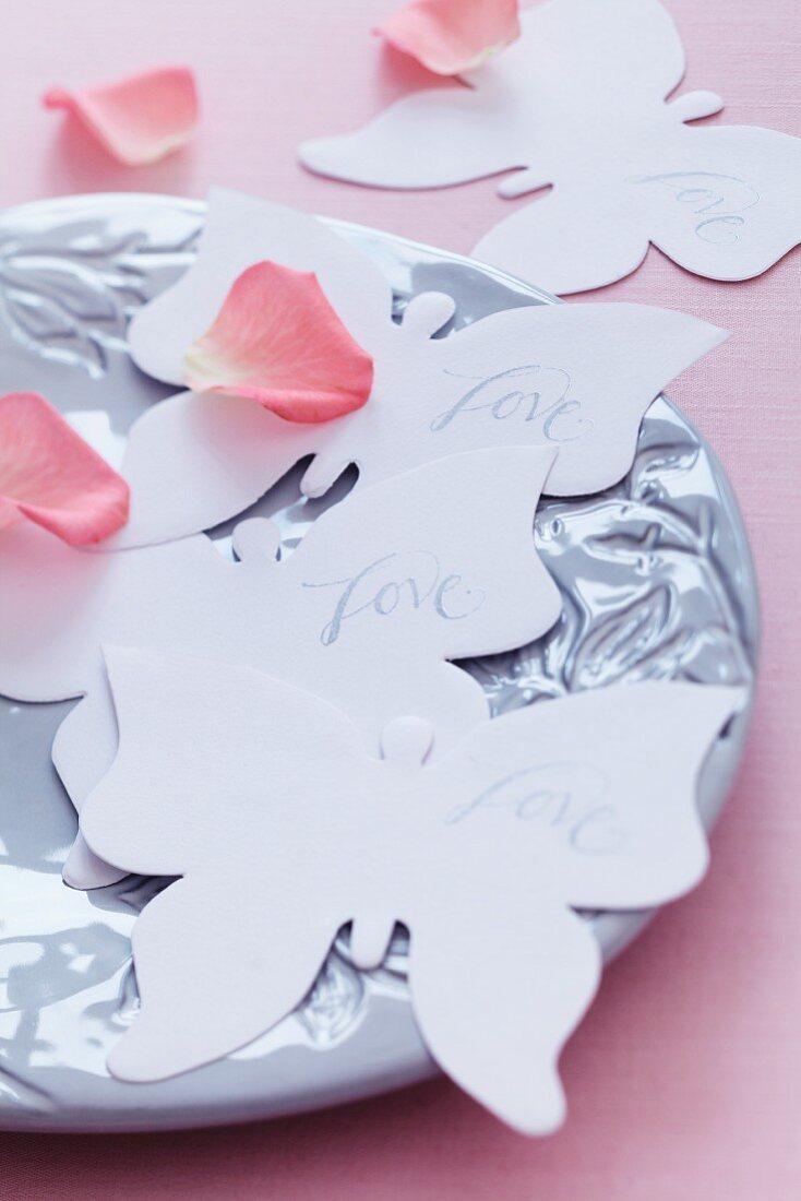 Paper butterflies & rose petals decorating table