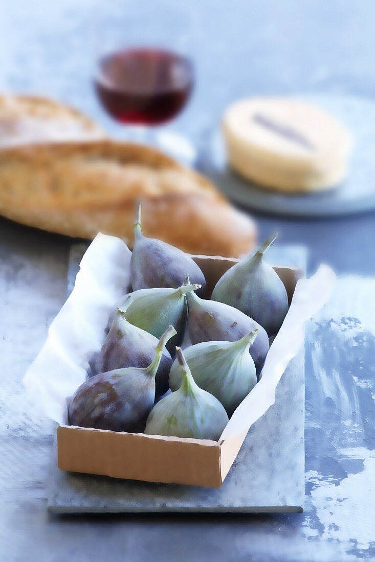 Figs in a box, with bread, cheese and wine in the background