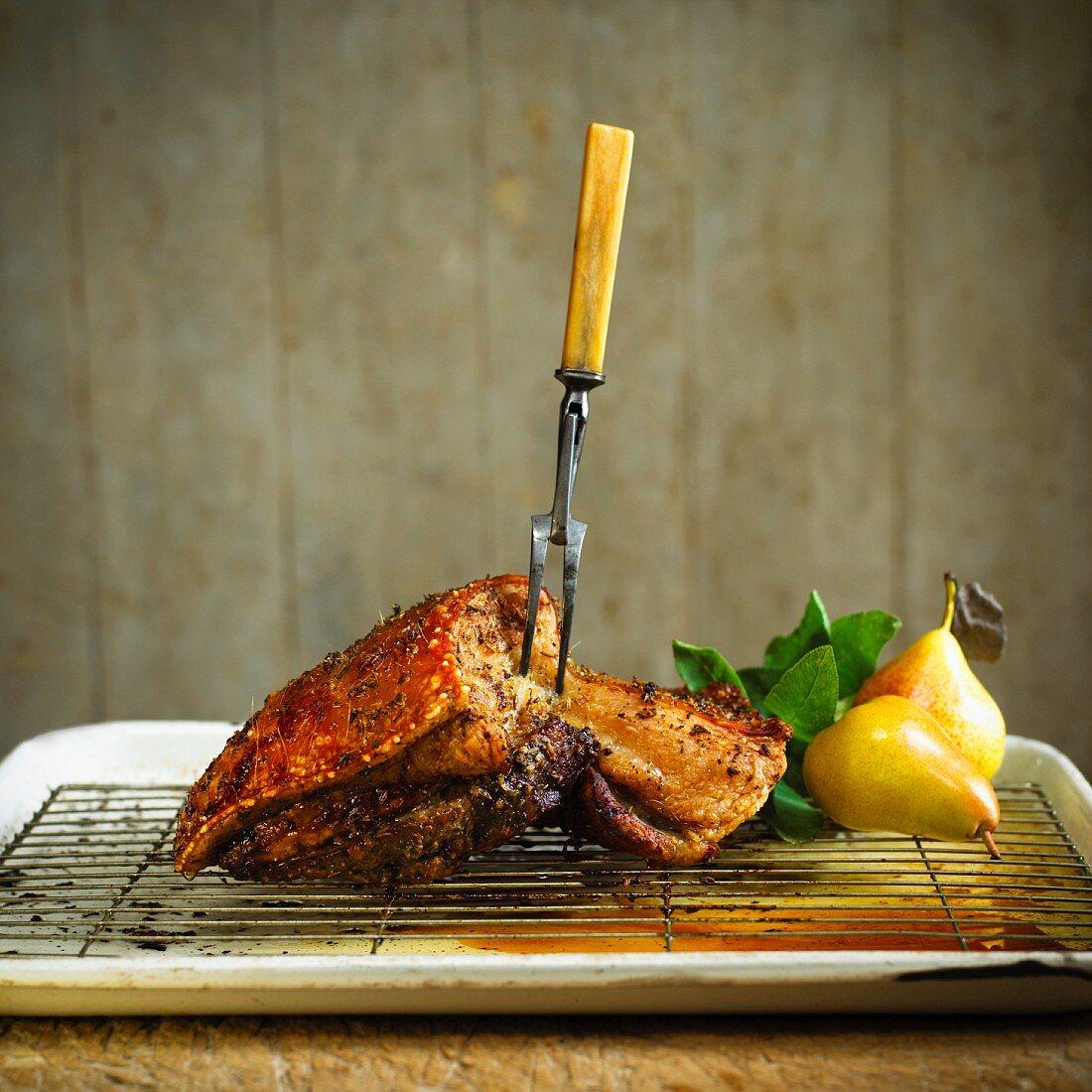 Crispy roasted pork belly with a meat fork