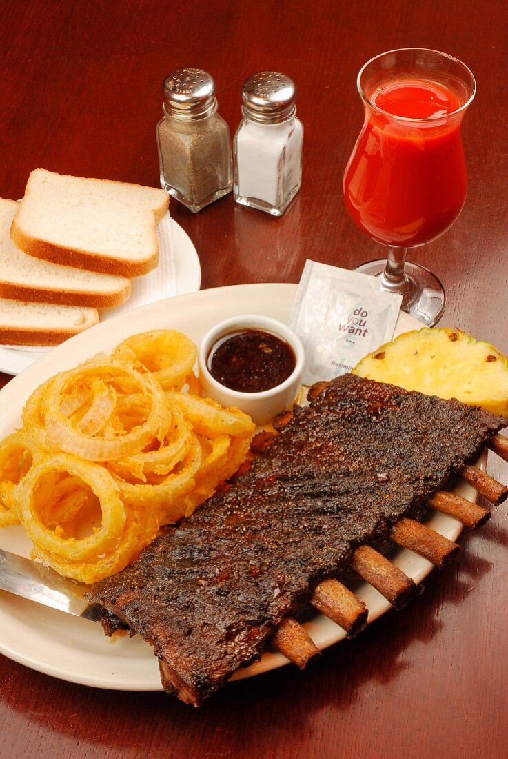 Lamb ribs with fried onion rings and tomato juice