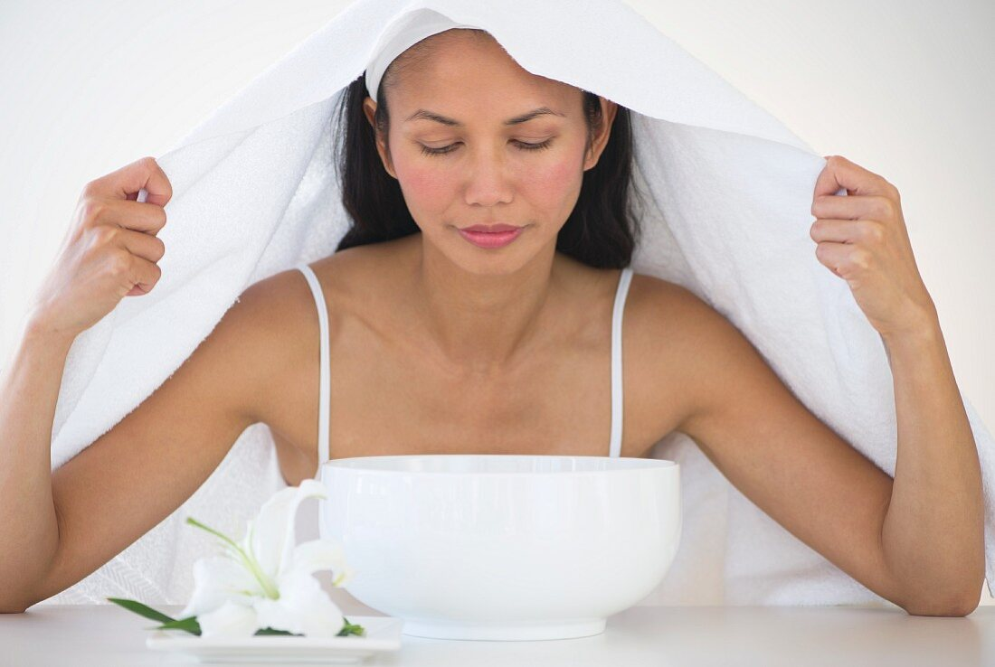 Woman under towel having steam beauty treatment