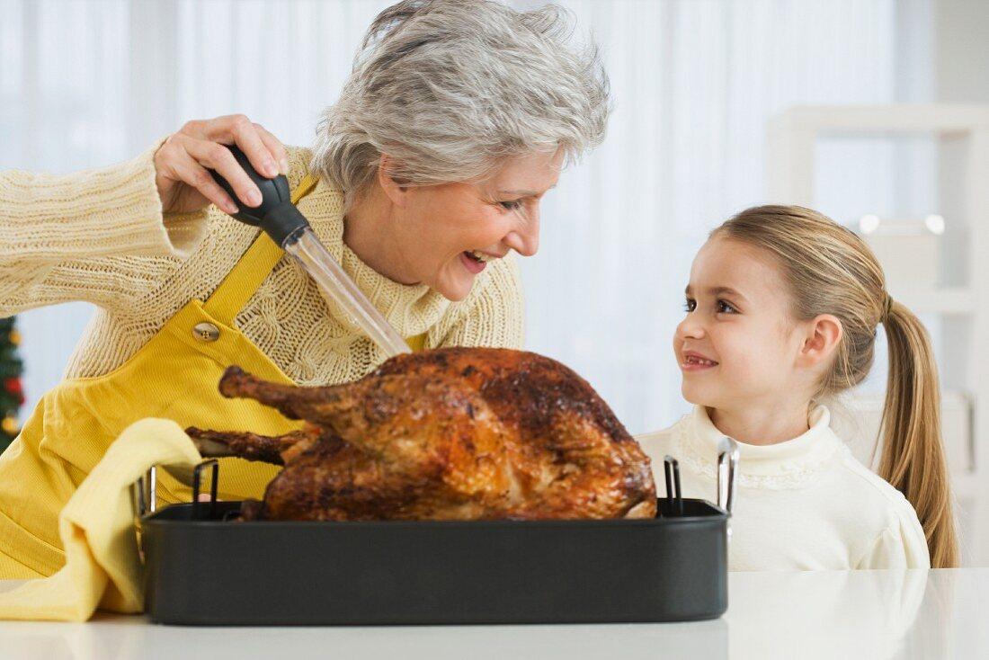 Grandmother and daughter basting roast turkey