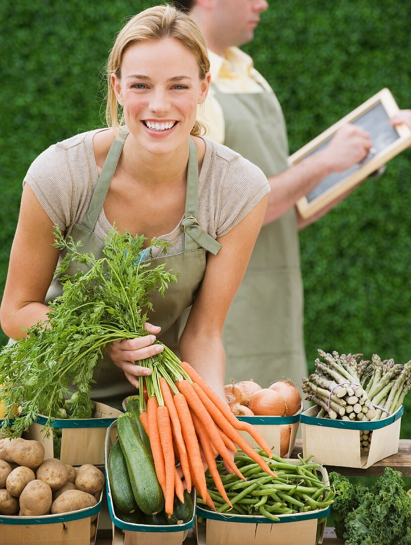 Woman next to baskets of vegetables