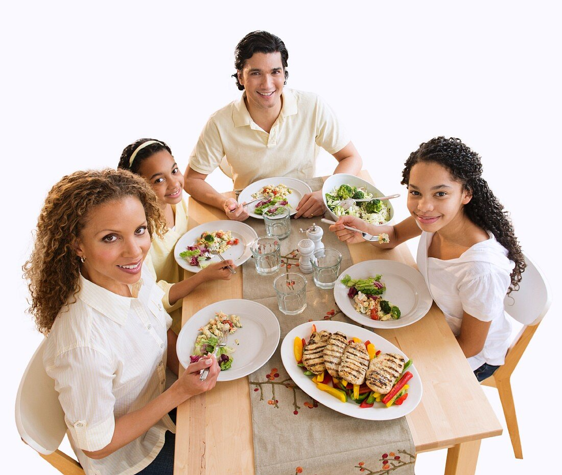 Portrait of parents with daughters (10-13) eating dinner