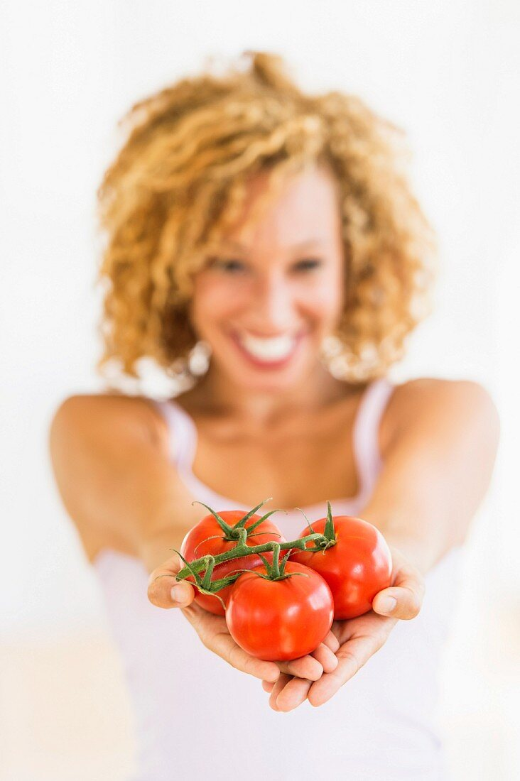 Portrait of young woman holding tomatoes