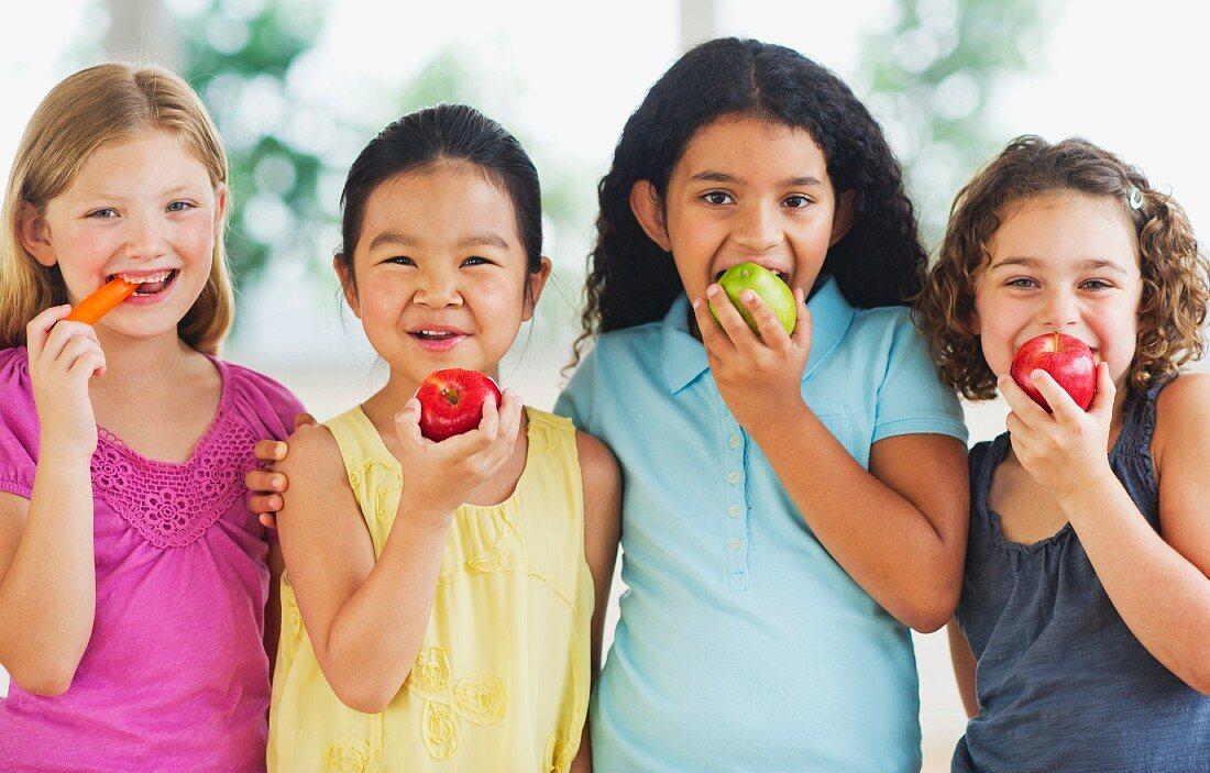 Portrait of girls (6-9) eating fruits