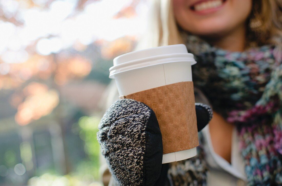 Woman wearing gloves holding coffee cup