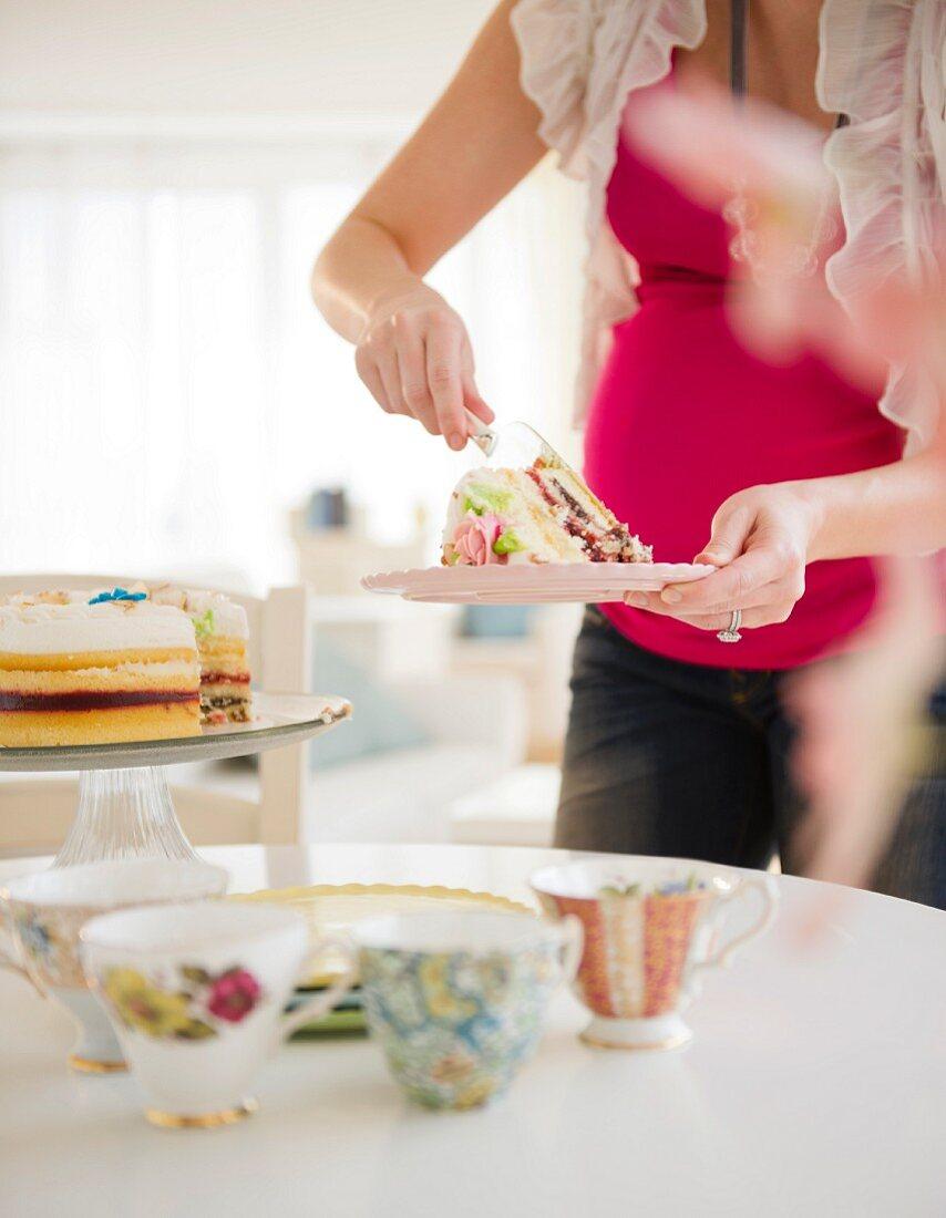 Pregnant woman serving cake