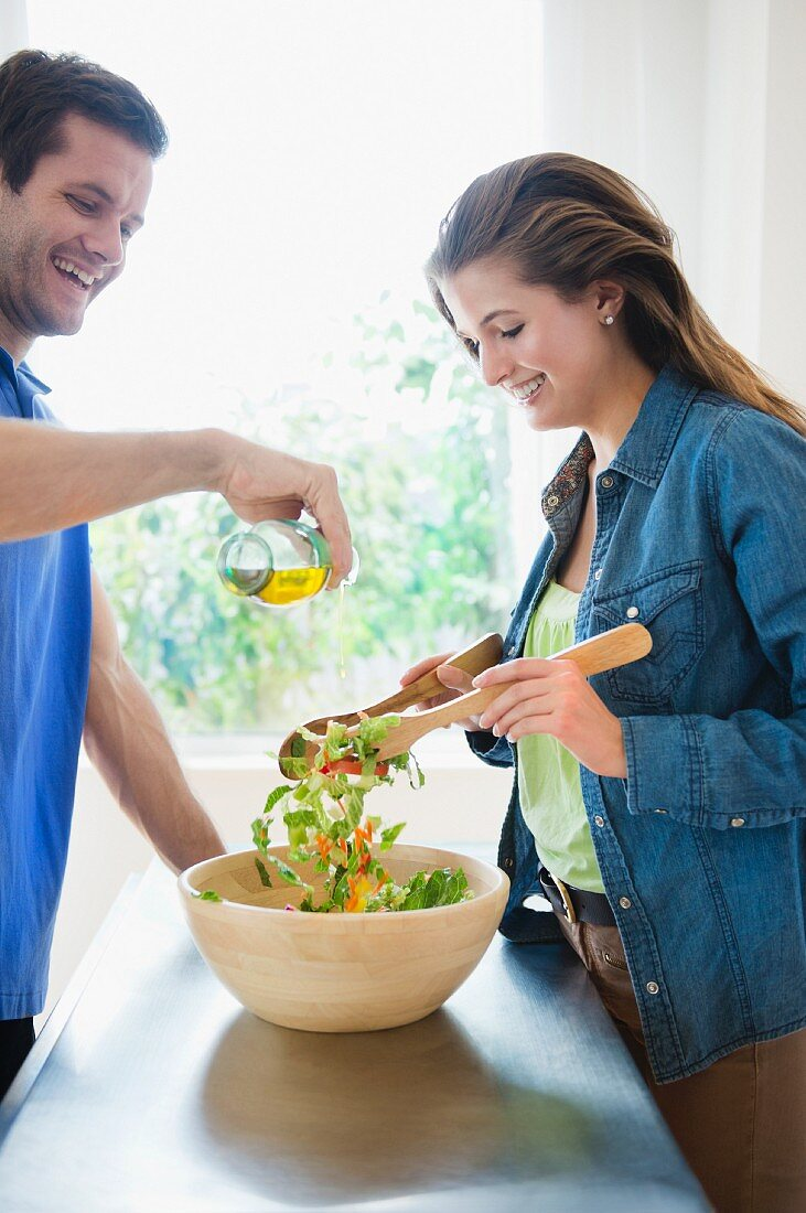 Happy young couple making salad