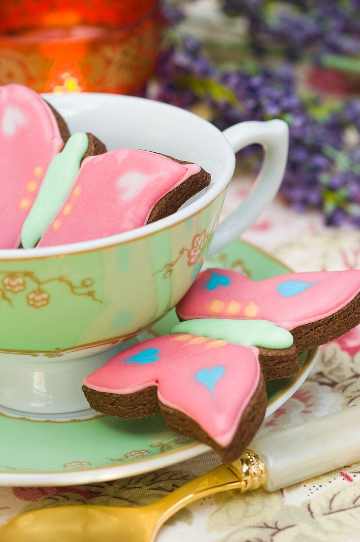 Butterfly cookies in a tea cup with saucer, Tea light. Lavender.