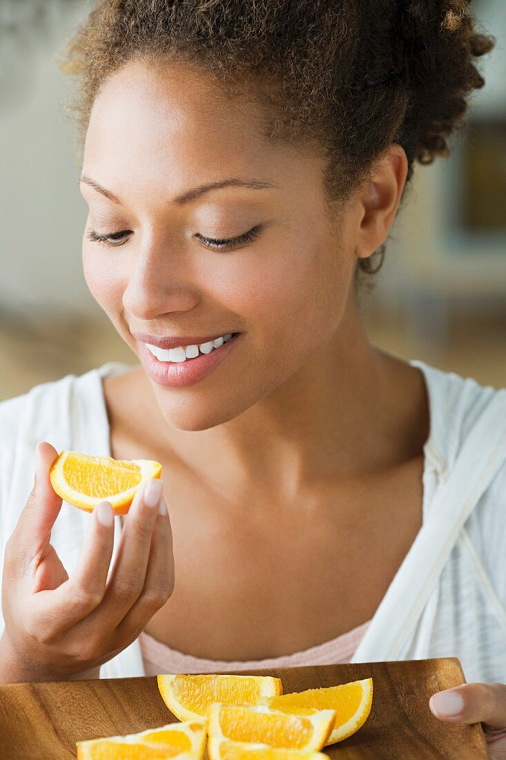 Portrait of attractive woman eating orange