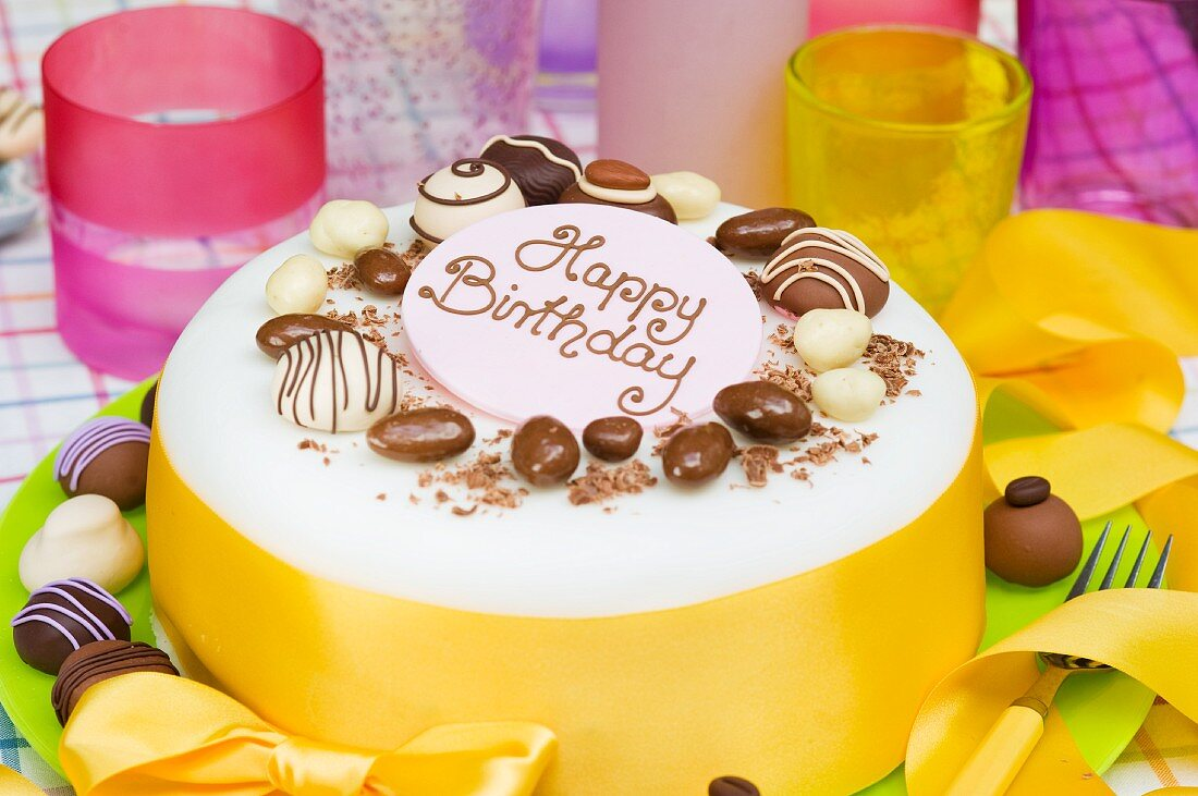 Birthday cake with chocolate candies and yellow bow