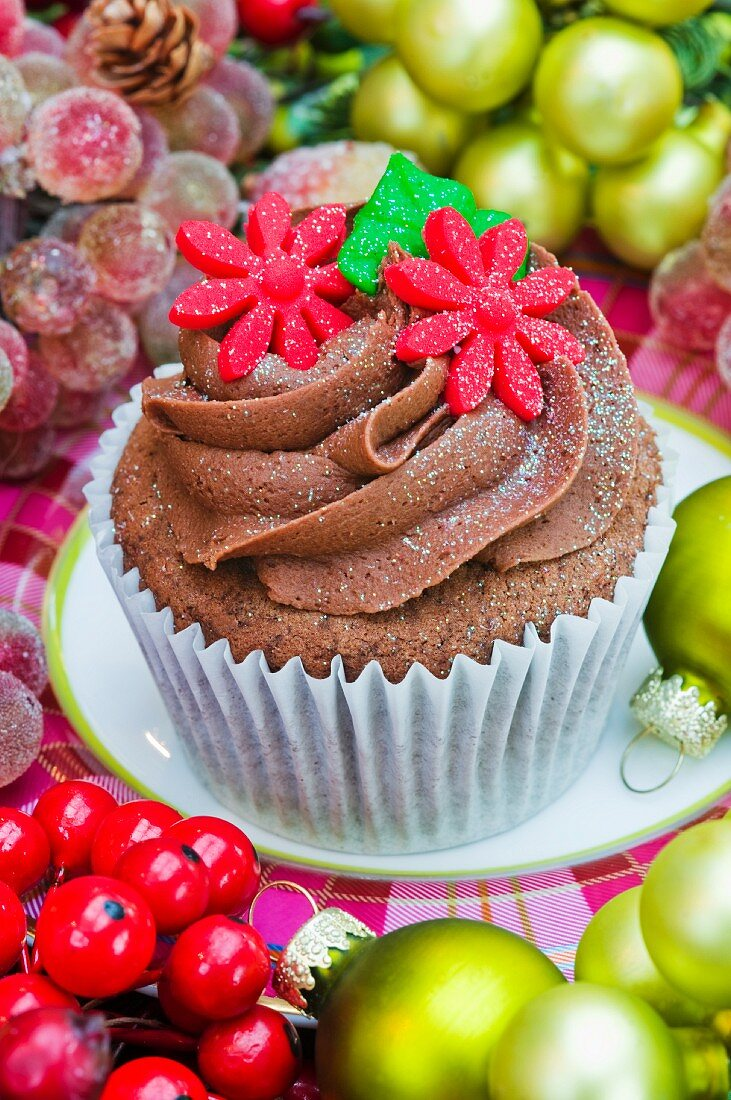Chocolate cupcake decorated with red sugar flowers for Christmas
