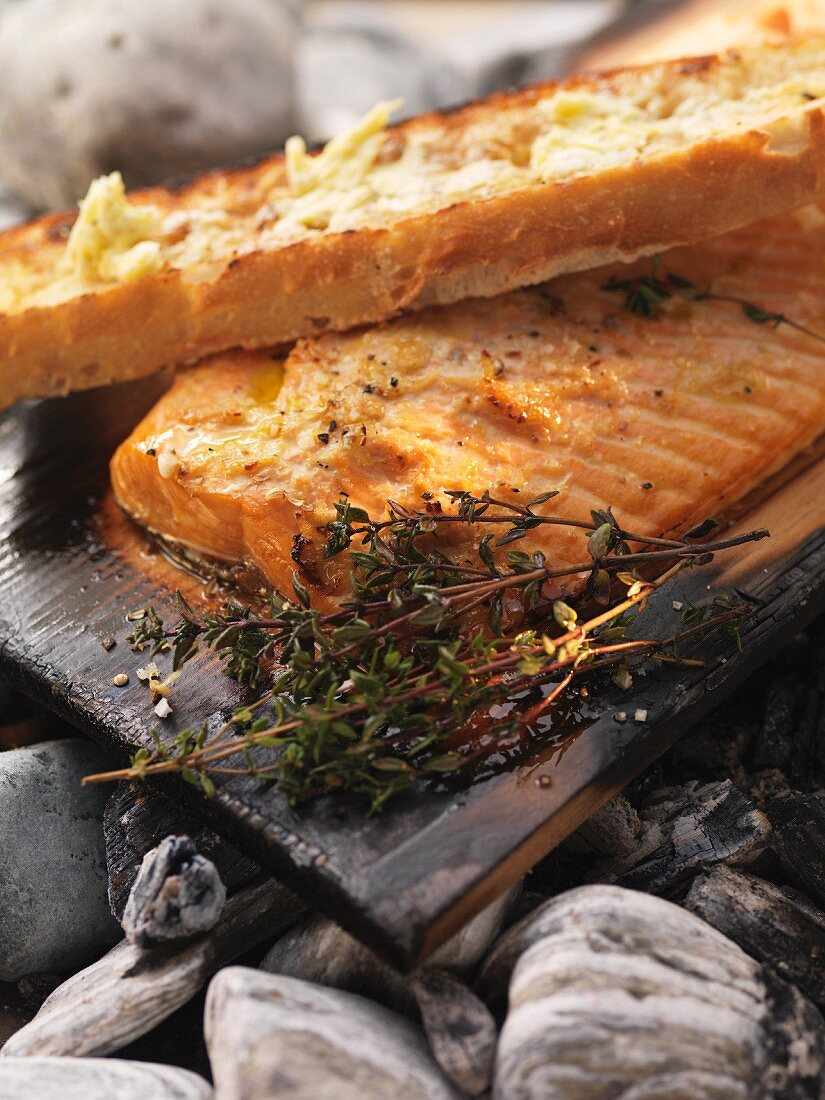 Salmon barbecued on cedar wood with thyme and garlic bread