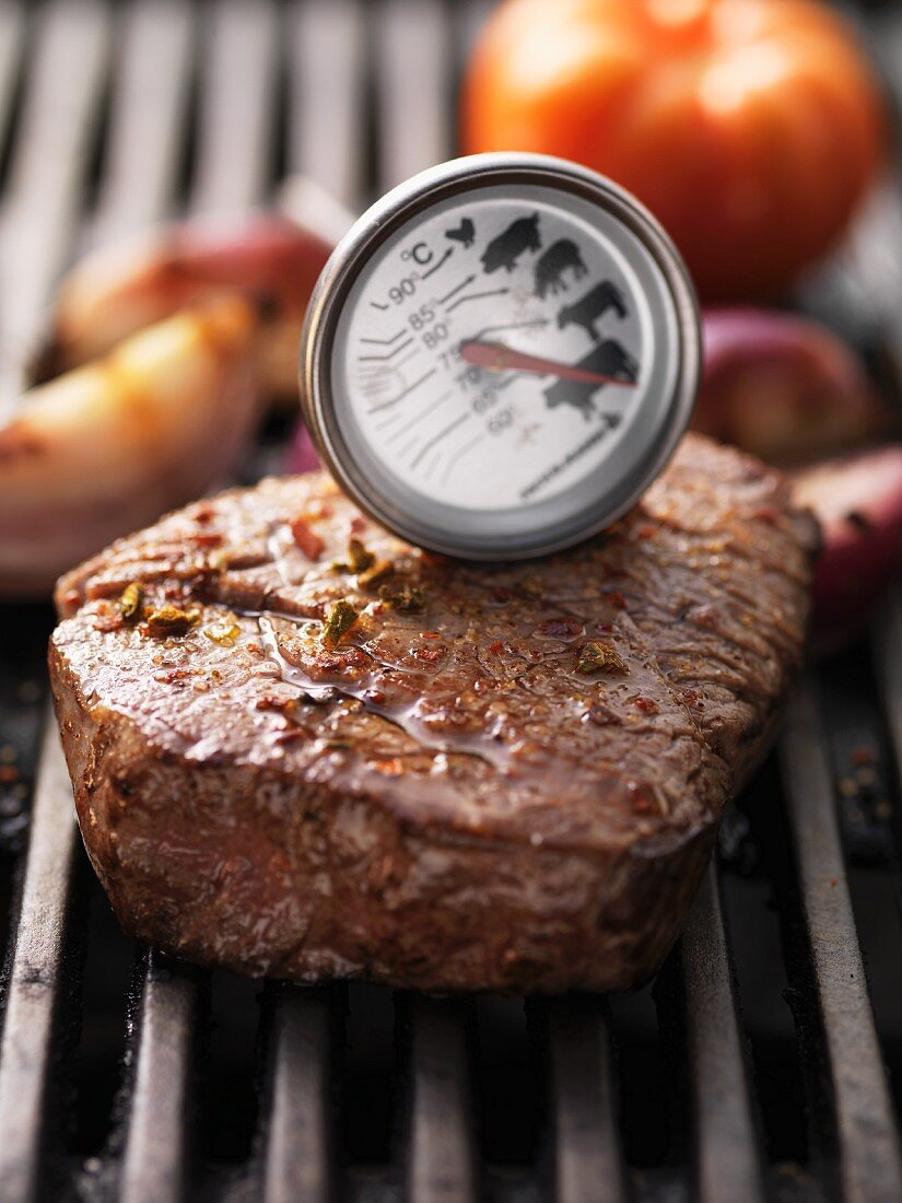 Barbecued beef steak with meat thermometer, on the barbecue