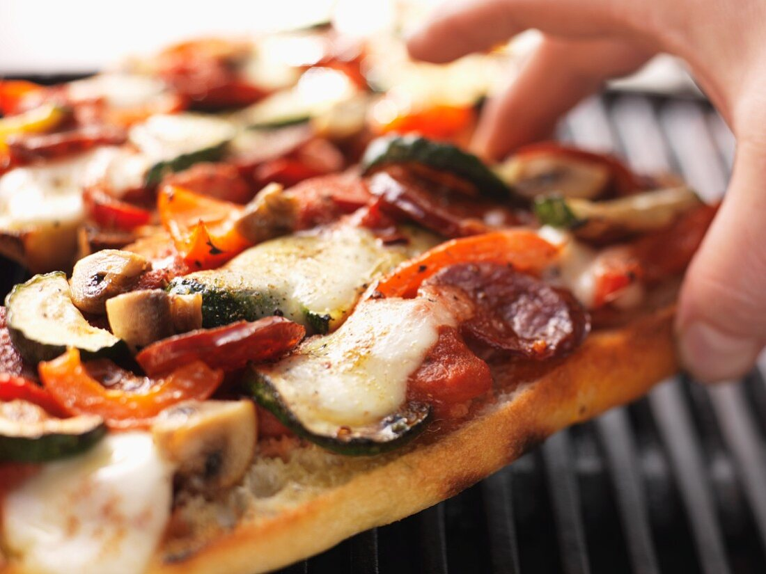Sausage, vegetable and mozzarella pizza cooked on the barbecue