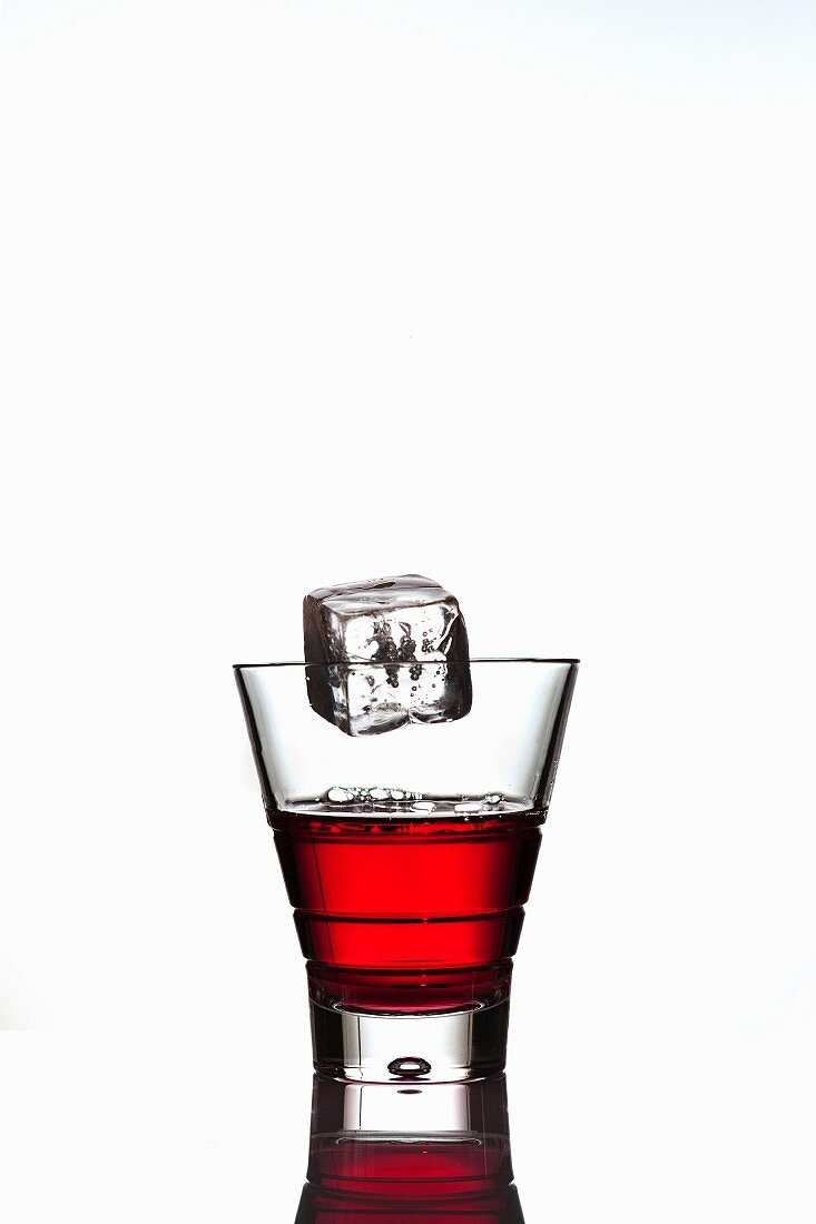 Ice cube falling into a glass of Campari