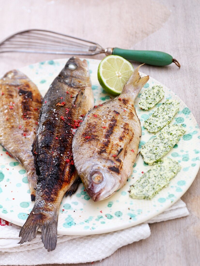 Grilled fish with herb butter and lemon