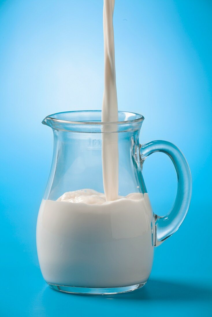 Pouring milk into a glass jug