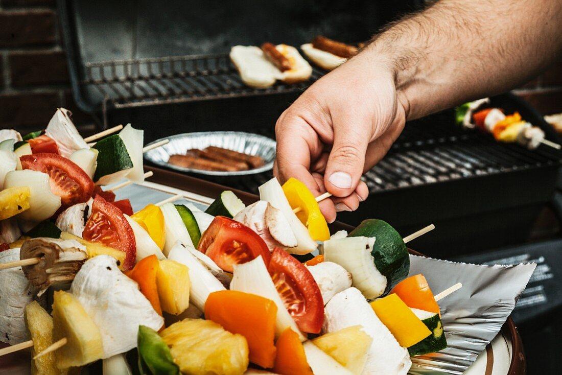 A man barbecuing vegetable skewers