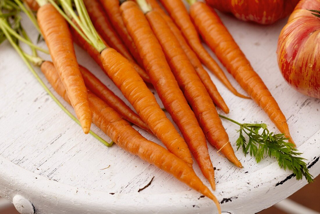 Carrots and Tomatoes on a Distressed White Table