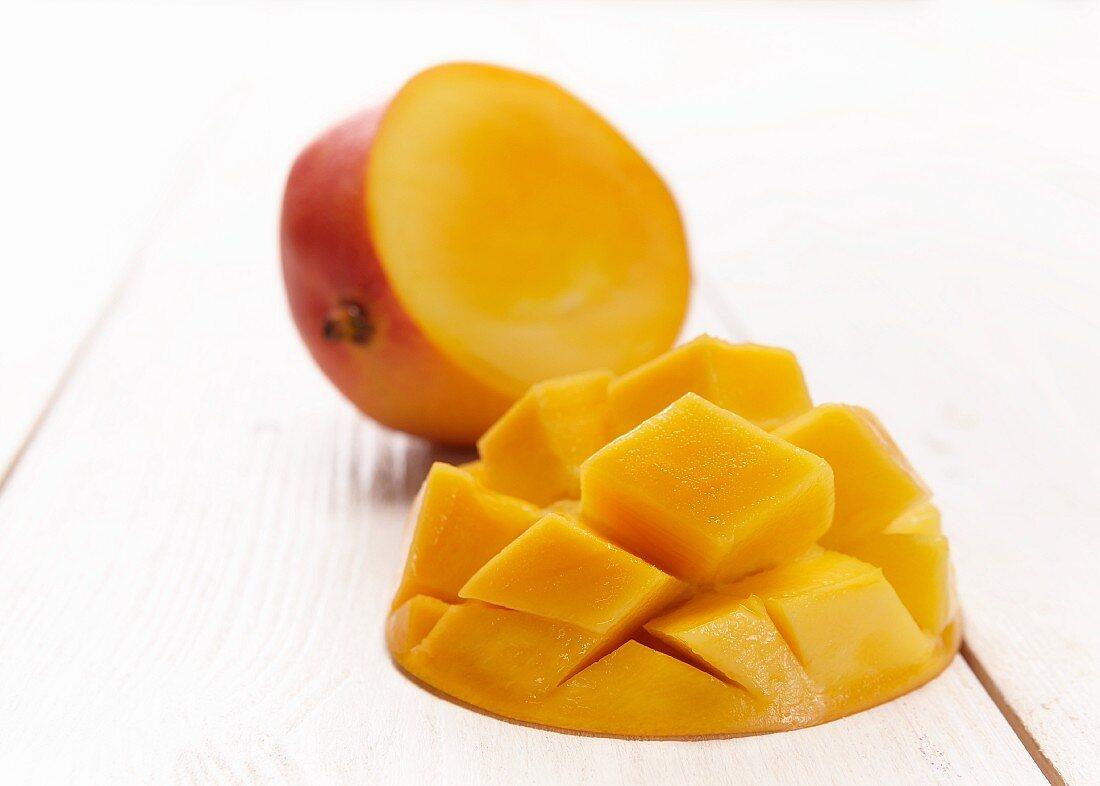 A mango cut in half, with one half cut into chunks in a diamond pattern