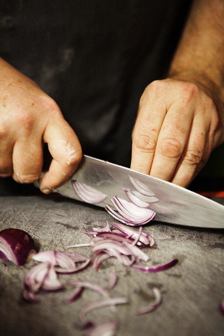 A man cutting a red onion