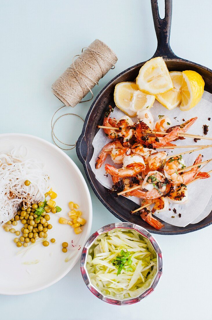 Prawn skewers with lemon wedges in a frying pan, alongside string, rice noodles and salad